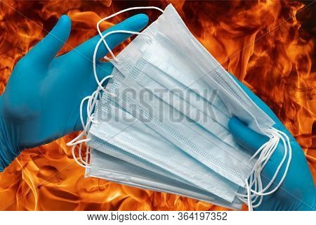 Human Hands Holding Lot Protective Face Masks In Blue Medical Gloves On Background Flames Of Strong
