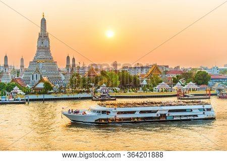 Beautiful Temple Of Dawn Or Wat Arun And Boats On Chao Phraya River At Sunset With Shining Sun. Bang