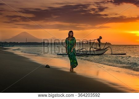 Attractive Woman In A Green Dress Walks Down The Beach At Sunset Gili Air East Of Bali Indonesia