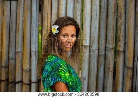 Young Woman With Plumeria Flower In Her Hair Against Bamboo Fence