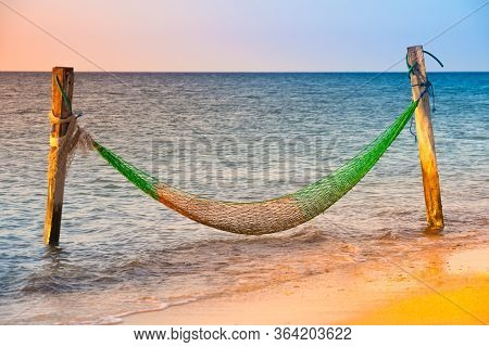 Empty Hammock Over The Blue Ocean At Sunset.