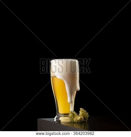 Pint Of Cold Pale Beer With Froth Leaking Over The Glass And Some Hops Placed On A Bar Counter With