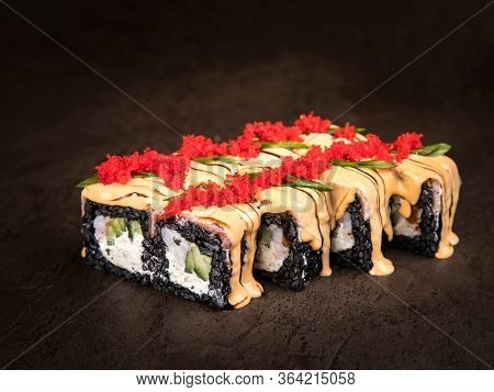 Japanese Rolls, Abundantly Doused With Sauce And Garnished With Tobiko Caviar And Chopped Green Onio