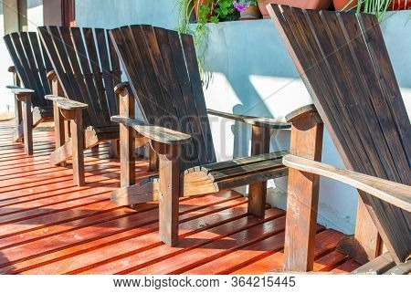 Empty Adirondack Arm Chairs In Row On Wood Deck , Focus On The Arm Of The Chair On A Bright Sunny Da