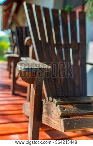 Vertical Image, Empty Adirondack Arm Chairs In Row On Wood Deck , Focus On The Arm , Shallow Depth O