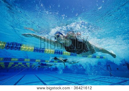 Female participants gushing through water in swimming competition