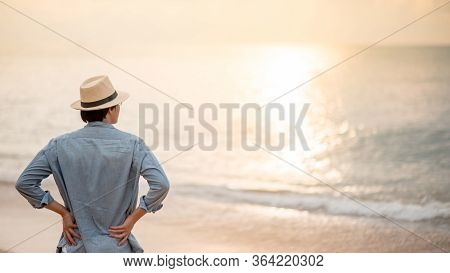 Asian Man Tourist Wearing Hat Standing On Tropical Island Beach Enjoy Looking At Sunset. Relaxing Ho