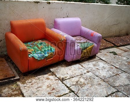 Abandoned Worn Out Old Armchairs Thrown In The Street - Social Poverty Symbolic Image