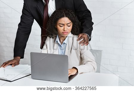 Sexual Harassment In Office Concept. African American Boss Molesting His Female Employee At Workplac
