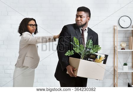 Job Loss And Unemployment Concept. Female Boss Firing African American Employee In Office