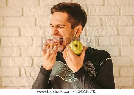 Greedy Young Man In Protective Face Mask Eat Sweet Donut And Hold Apple In Hand. Sugar Temptation Of