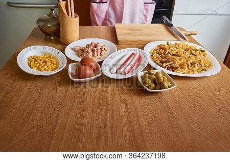 Table In A Kitchen With Several Foods On It. Ingredients For Making A Pasta Salad
