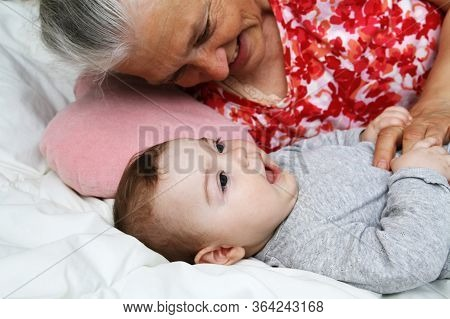 Grandmother Play With Her Baby Granddather Indoors. Senior Woman With Girl. Multi Generation Family