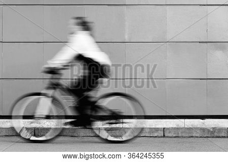 A Man In Blurry Focus Is Riding A Fast Bicycle Against A Static Black-and-white Wall. Athletic Girl
