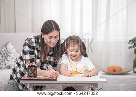 A Mother With A Child Sits At The Table And Does Homework. The Child Learns At Home. Home Schooling.