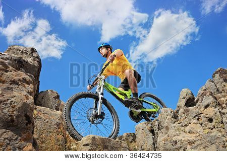 Person riding a mountain bike amid rocks on a sunny day against a blue sky and clouds, low angle view