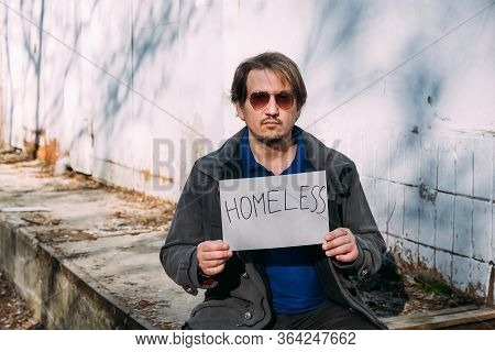 Misery Man Sitting On Garbage Dump And Holding Piece Of Cardboard With Homeless Inscription.