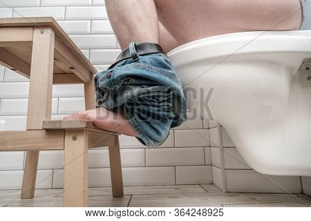 Man Sitting On Toilet Bowl Properly, He Put Feet On A Small Stool In A Squatting Position, During Th