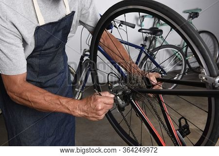 Bicycle Repair. A Bike Tech making adjustments to the derailleur in his workshop.