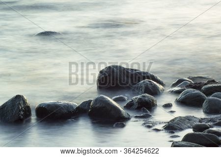 Long Exposure Of Sea And Rocks. Boulders Sticking Out From Smooth Wavy Sea. Tranquil Scene.