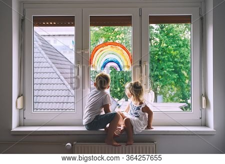 Smiling Little Children On Background Of Painting Rainbow On Window. Photo Of Kids Leisure At Home,