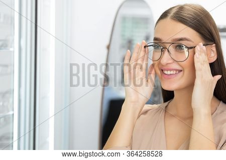 Choosing Glasses Concept. Portrait Of Beautiful Girl Picking New Specs At Optical Shop, Copy Space