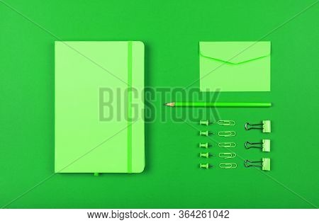 Neatly Organized Stationery Flat Lay Of Pastel Green Notebook, Envelope, Pencil, Office Clips, Binde