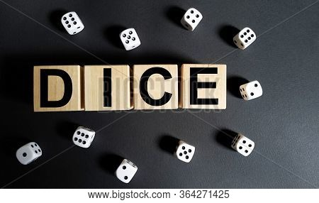 White Dice Disorganized On A Black Background. The Word Dice Is Written On Wooden Cubes.