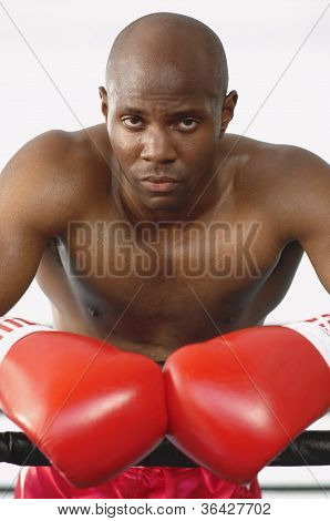 Portrait of a serious African American boxer standing by the boxing ring