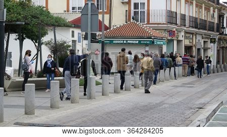 Crowd Of People Queuing Outside Bank On Restricted Opening Day