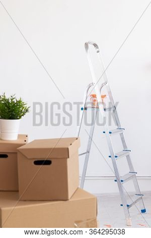 Ladder With Paint In Bucket Near Color Wall Indoors. Renovation And Redecoration Concept.