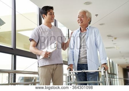 Happy Senior Asian Woman Talking To Physical Therapist In Rehab Center