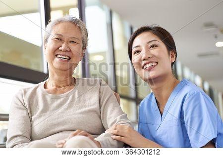 Asian Senior Woman And Her Caregiver Looking At Camera Smiling