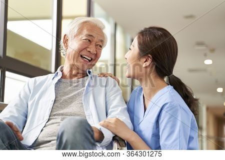 Young Friendly Asian Female Caregiver Talking Chatting To Happy Senior Man In Hallway Of Nursing Hom