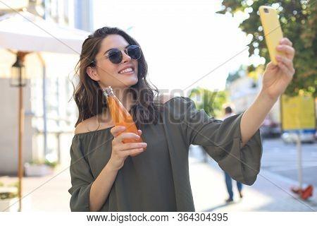 Smiling Beautiful Brunette Woman Walking Outdoors By Street, Take Selfie By Mobile Phone, Drinking J