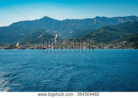 White Yachts And Catamarans In A Bay Near A Tropical Island. Sailing Yacht And Motor Catamaran For C