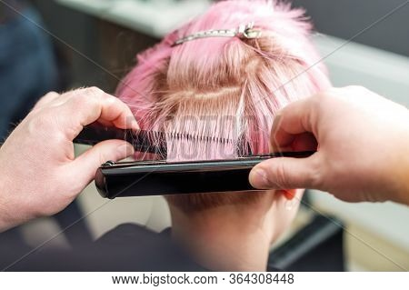 Close Up Hairdresser Is Straightening Short Pink Hair With Hair Iron In Beauty Salon, Concept Barber