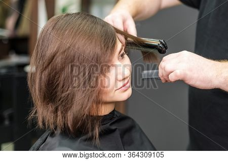 Professional Hairdresser Straightening Brown Hair With Hair Straighteners In Beauty Salon