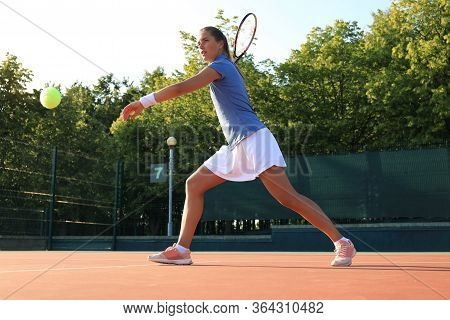 Professional Equipped Female Tennis Player Beating Hard The Tennis Ball With Racquet.