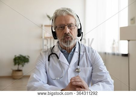 Older Doctor Videoconferencing Talking To Web Camera Consulting Virtual Patient