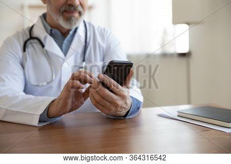 Senior Male Doctor Using Mobile Phone Technology Apps At Desk