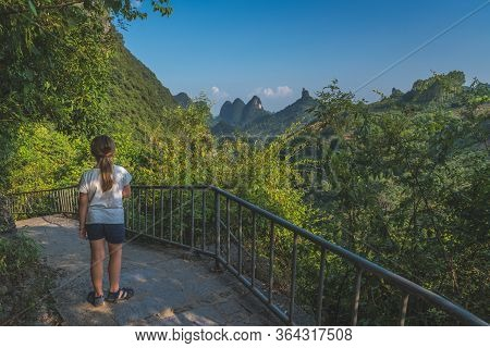 Little Girl Standing On The Sidewalk In The Middle Of The Mountains And Enjoying The View Of Karst M