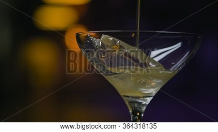 Close-up In Transparent Glass With Ice Pour Shiny Drink. Stock Footage. Thick Iridescent Alcoholic D