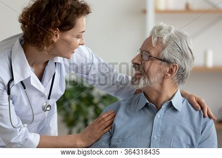 Caring Female Doctor Embracing Helping Happy Senior Male Patient