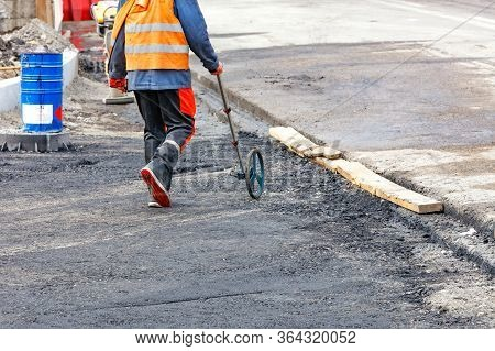 An Engineer Measuring Road Distances With A Measuring Wheel Determines The Required Amount Of Asphal