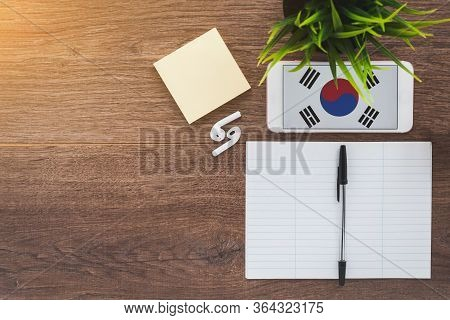 Republic Of Korea Flag On Smartphone On A Wooden Table, Notebook And Pen, Study Concept