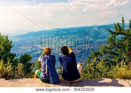 Two Guys Are Sitting And Looking Into The Distance And The Mountains, Discussing Something And Showi