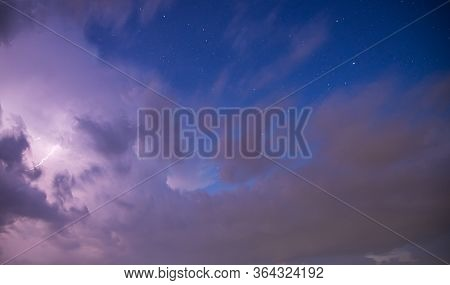 Dramatic Storm Clouds With Blue Sky, Stars And Lightening Bolt