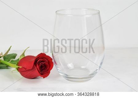 A No Stem Wineglass Chills Romantically Next To A Long Stemmed Red Rose.