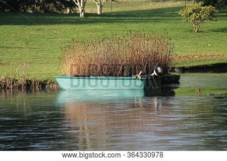 A Fibreglass Dinghy Boat Moored On A Small Lake.